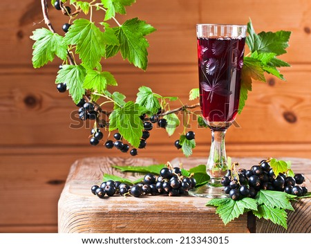 black currant liquor and ripe berries  on  wooden table - stock photo