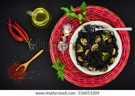 Black cuttlefish spaghetti, garlic, spices, olive oil and chili on dark grunge backdrop. Top view. - stock photo