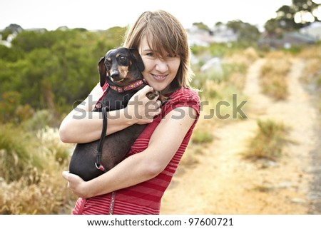 Black Dachshund dog being hugged by young lady dressed in short red summer shirt - stock photo