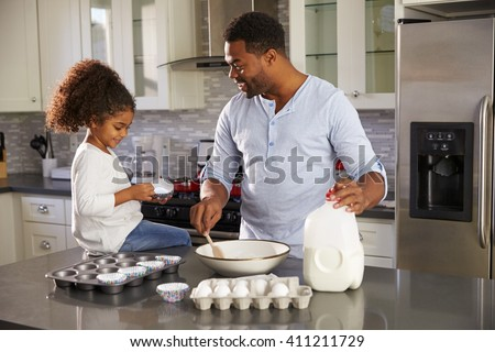 Black dad and young daughter baking together in the kitchen - stock photo