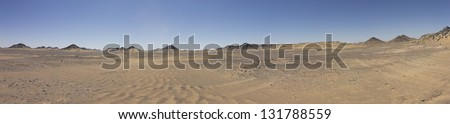 Black desert panorama with desert mountains on the horizon, Oasis area, Egypt. Black rock was created by the volcanic activity long time ago - stock photo
