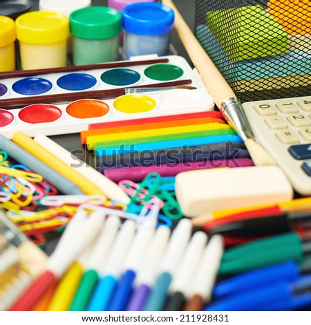 Black desk's surface covered with multiple stationery office supplies as a background back to school composition - stock photo