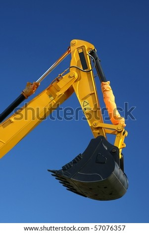 Black digging bucket on the end of a yellow hydraulic arm of a digging machine - stock photo
