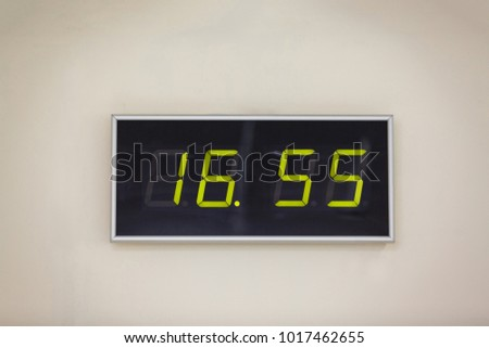 Black digital clock on a white background showing time 16 hours 55 minutes