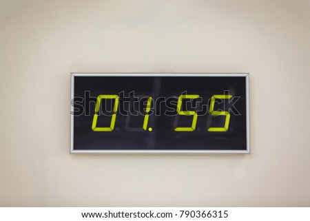 Black digital clock on a white background showing time one hours 55 minutes