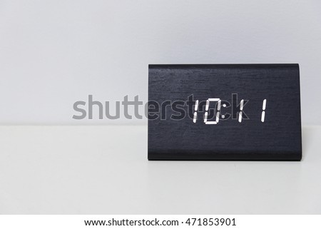 Black digital clock on a white background showing time 10:11 (ten hours eleven minutes)