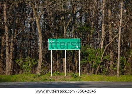 Black direction sign at a crossroads, trees behind - stock photo