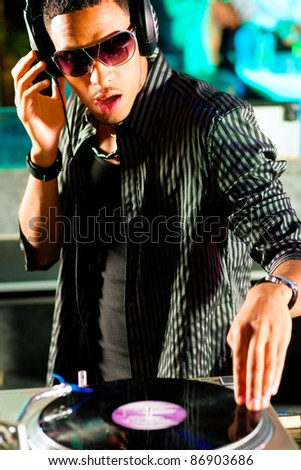 Black DJ in a club at the turntable - stock photo