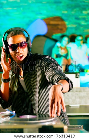 Black DJ in a club at the turntable, in the background the crowd is cheering - stock photo
