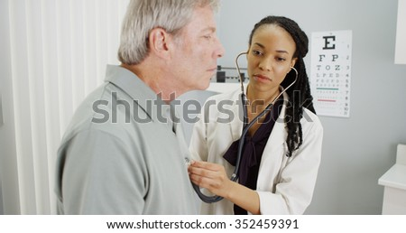 Black doctor listening to senior breathing - stock photo
