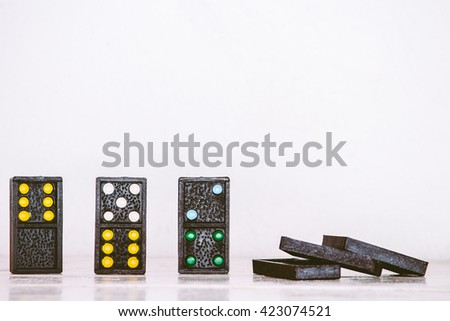 Black domino on wooden table - stock photo