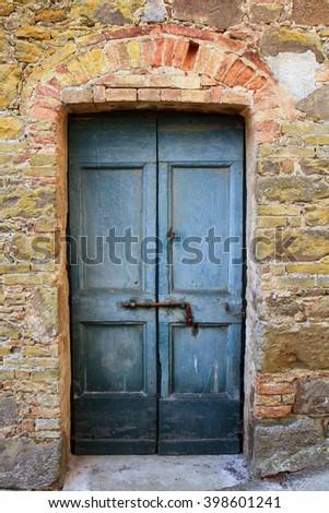Black door in a stone wall, Montalcino, Tuscany, Italy - stock photo