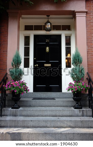 Black door in Boston on a stately brownstone in the beacon hill area. Ornate flower urns and elaborate door knocker. Lights on inside the house can be seen from the street. - stock photo