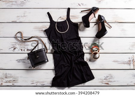 Black dress, shoes and jewelry. Black female outfit on table. Glamorous dark clothes with purse. Retro purse and modern clothing. - stock photo
