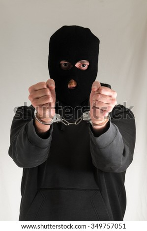 Black Dressed Young Man Trapped in Hancduffs - stock photo