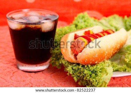 black drink and hot dog over lettuce over orange table - stock photo