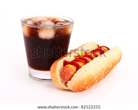 black drink and hot dog over lettuce over white background - stock photo
