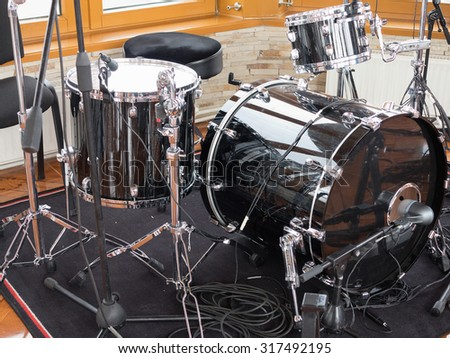 Black drum kit, cables and microphones closeup detail - stock photo