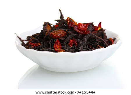 Black dry fruit tea leaves in plate isolated on white