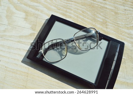 black e-book and reading glasses on wooden table - stock photo