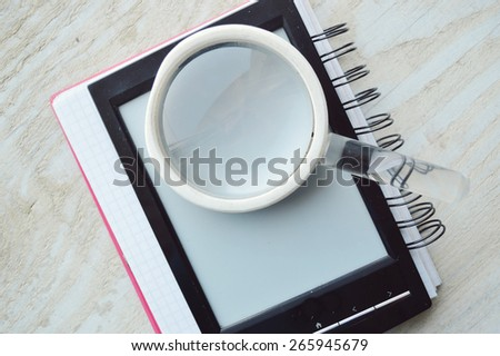 black e-book  for reading,reading glasses.red notebook for records - stock photo