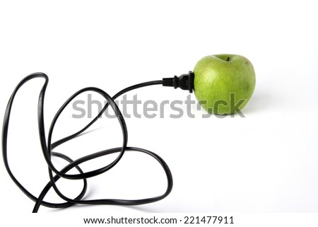 Black electric cable stab in fresh green apple  - stock photo