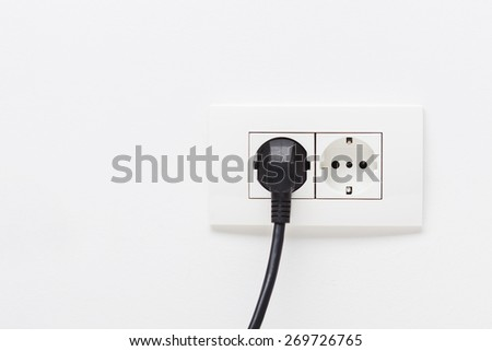Black electric chord plugged into a white electricity socket on white background - stock photo