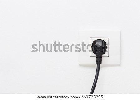 Black electric cord plugged into a single electric socket on white background