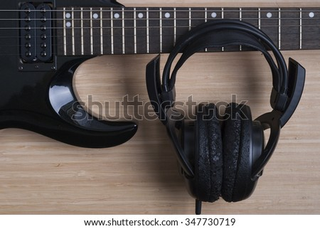 black electric guitar and headphones on a wooden background texture - stock photo