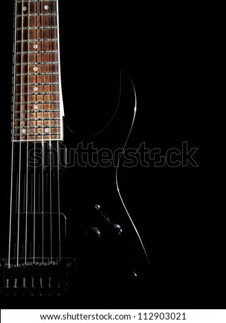 Black electric guitar with seven strings close up isolated on black background - stock photo