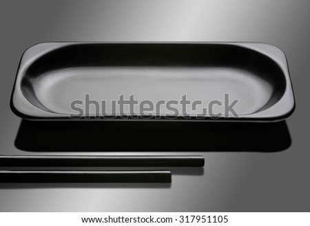 Black empty plate with two japanese sticks  - stock photo