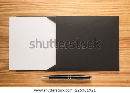 Black envelope with white paper and pen on the table  - stock photo