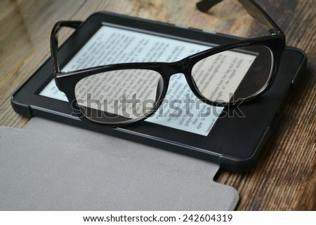 Black ereader with retro glasses on wooden table - stock photo