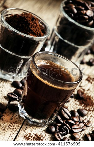 Black espresso coffee and ingredients for cooking: roasted coffee beans, ground coffee, Turkish coffee maker, vintage wooden background, selective focus - stock photo
