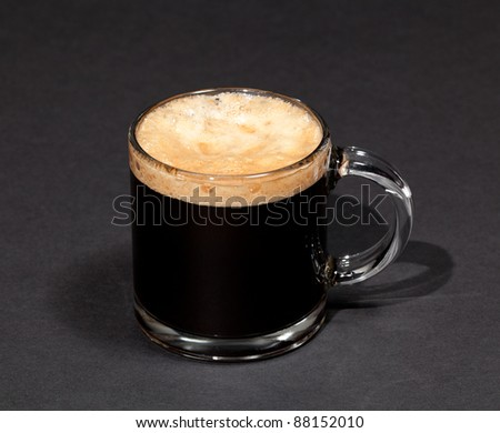 Black espresso coffee with heady froth in a glass mug or cup - stock photo