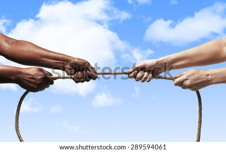 black ethnicity arms with hands pulling rope against white Caucasian race person in stop racism and xenophobia concept, immigration and multiracial  respect blue sky background - stock photo
