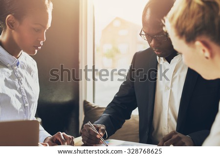 Black executive explain business plan in front of two female investors - stock photo
