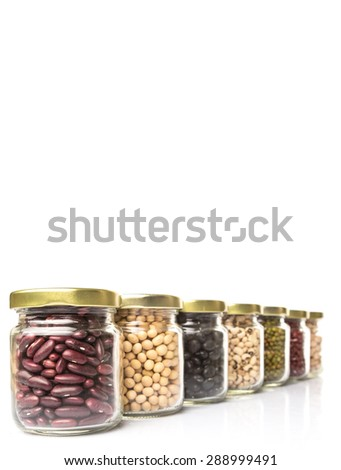 Black eye peas, chickpeas, adzuki beans, mung bean, soy beans, black beans and red kidney beans in mason jars over white background