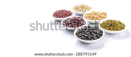 Black eye peas, mung bean, adzuki beans, soy beans, black beans and red kidney beans in white bowl over white background - stock photo