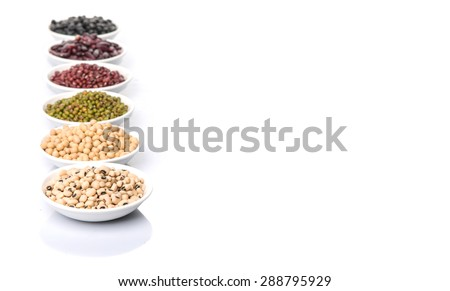 Black eye peas, mung bean, adzuki beans, soy beans, black beans and red kidney beans in white bowl over white background - stock photo