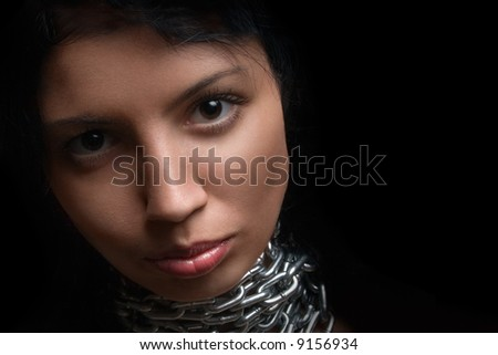 Black-eyed girl in chains on a black background - stock photo