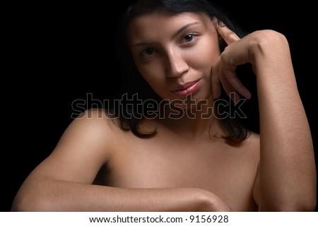 Black-eyed ironic smiling naked girl on a black background - stock photo
