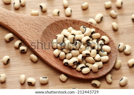 Black eyed peas in a wooden spoon. Close-up. - stock photo