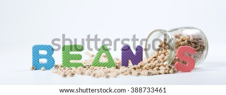 Black eyed peas in glass with BEANS Jigsaw Alphabet. Selective focus with shallow depth field. - stock photo
