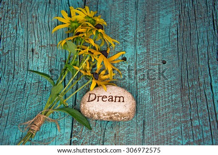 black-eyed susan bouquet on retro turquoise painted barn wood with inspirational rock - stock photo