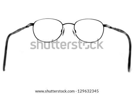 Black eyeglasses on white looking through lenses - stock photo