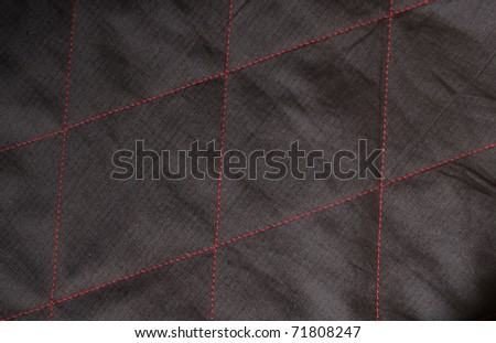 black fabric background  with red sewing - stock photo