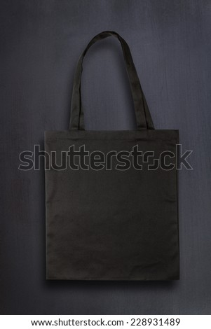 Black fabric bag against chalkboard background - stock photo