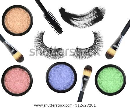 Black false eyelash, mascara, eyeshadows and brushes isolated on white background - stock photo