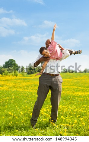 Black father playing with little boy holding him in airplane pose in the park - stock photo